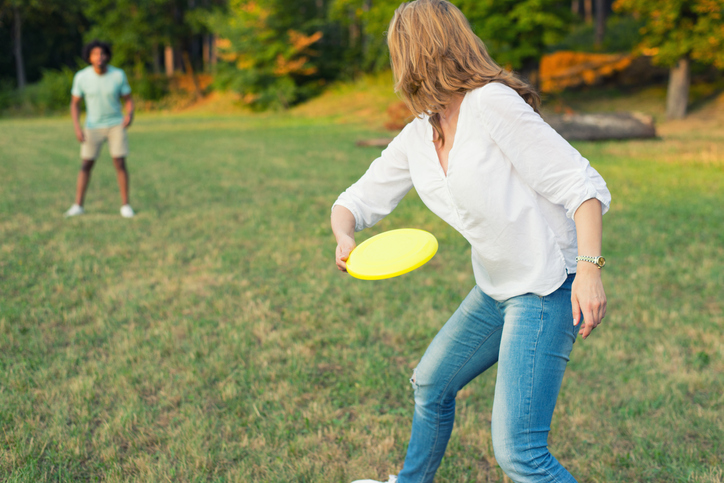 a woman throwing a frisbee