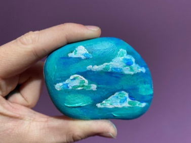 a hand holding a blue painted stone with clouds