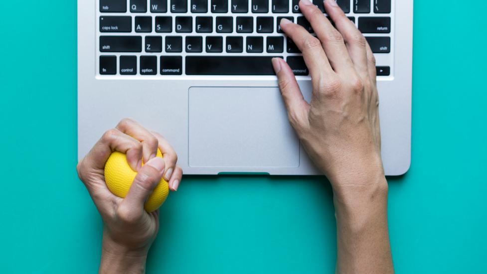a hand holding a stress ball next to a laptop