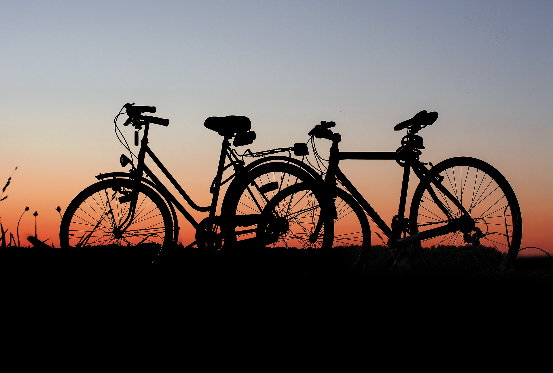 a bicycle parked in front of a sunset
