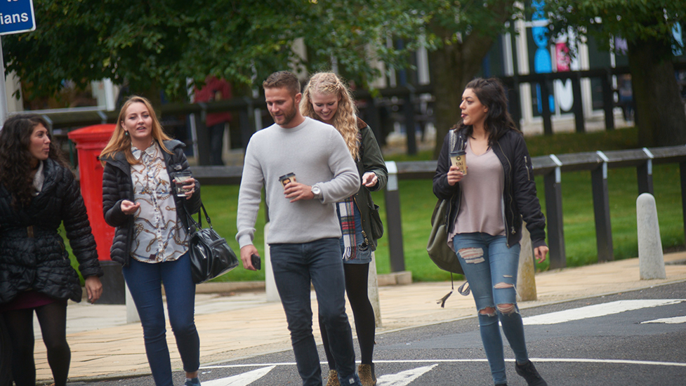 a group of people walking down the street talking on a cell phone
