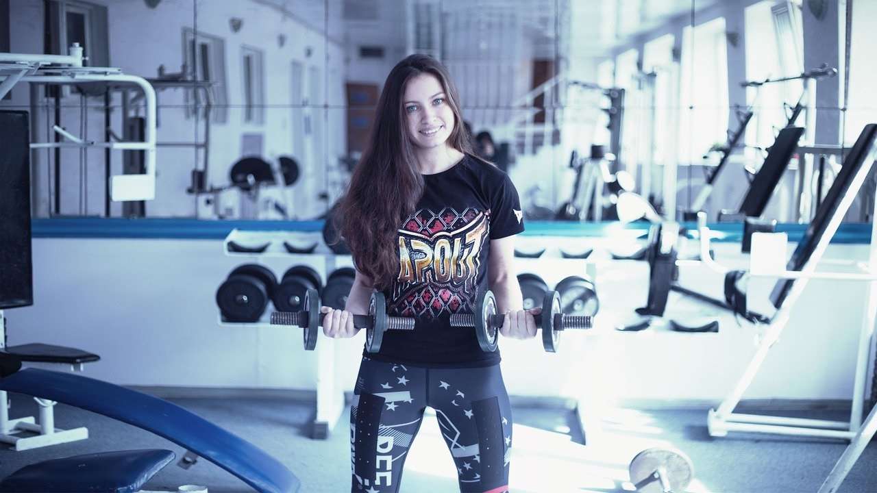 a woman in a gym lifting weights