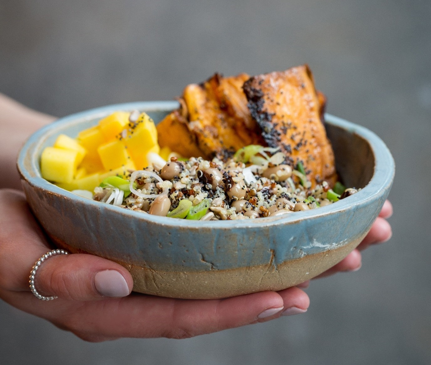 a hand holding a bowl of food