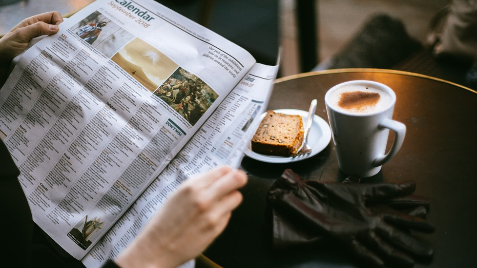 a person hsat at. table reading the newspaper with coffee