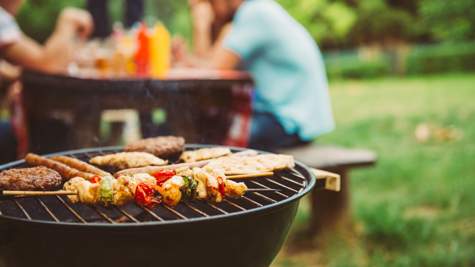 food on a bbq with people sitting on a bench in the background
