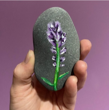 a hand holding a stone with heather painted on it