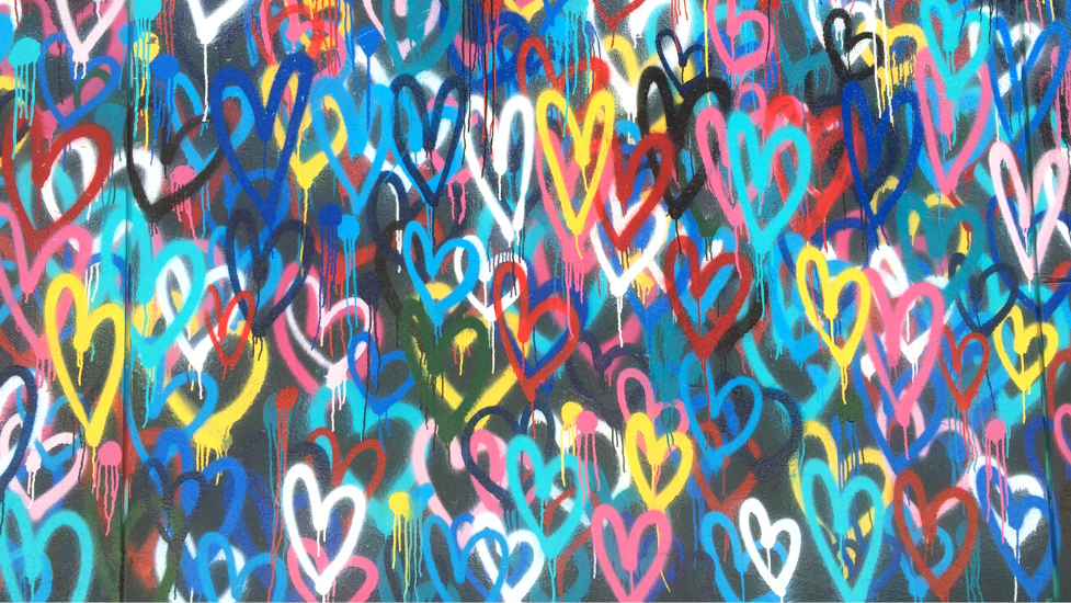 different coloured painted hearts on a wall