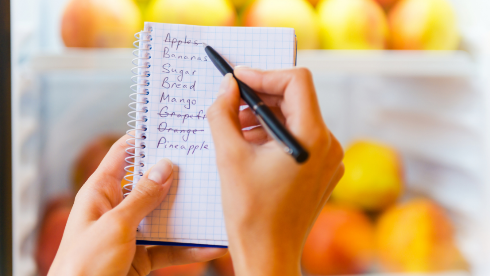 a person holding a piece of paper with a food shopping list