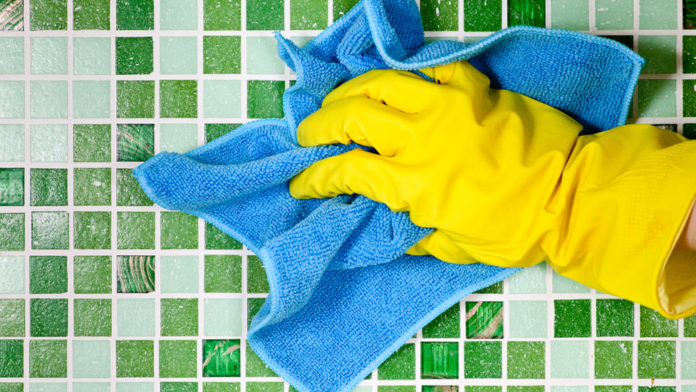 a person wearing marigold gloves wiping a tiled surface