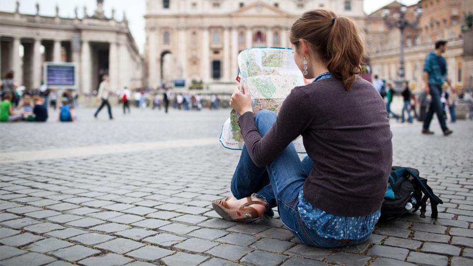 a woman sitting on a sidewalk