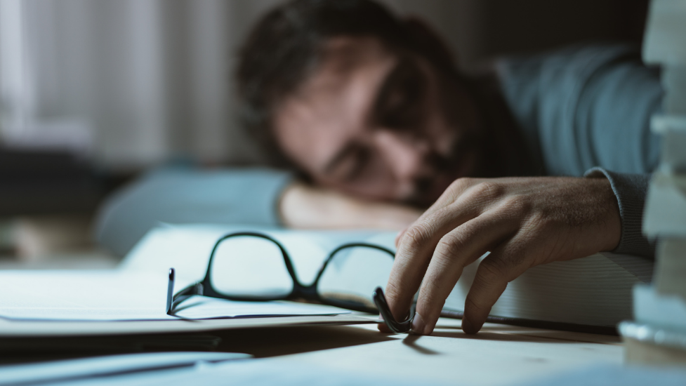 a close up of a person asleep on some books