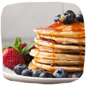 a pile of pancakes on a plate next to some fruit