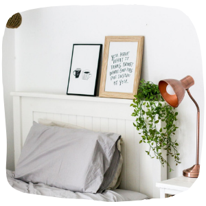 a bed with a plant hanging down next to it
