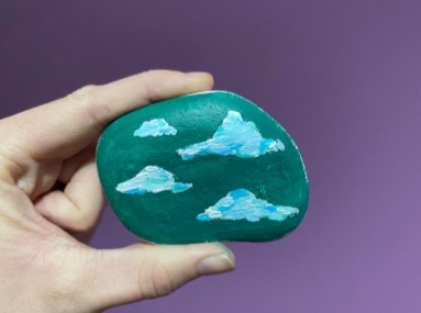 a close up of a hand holding a painted stone