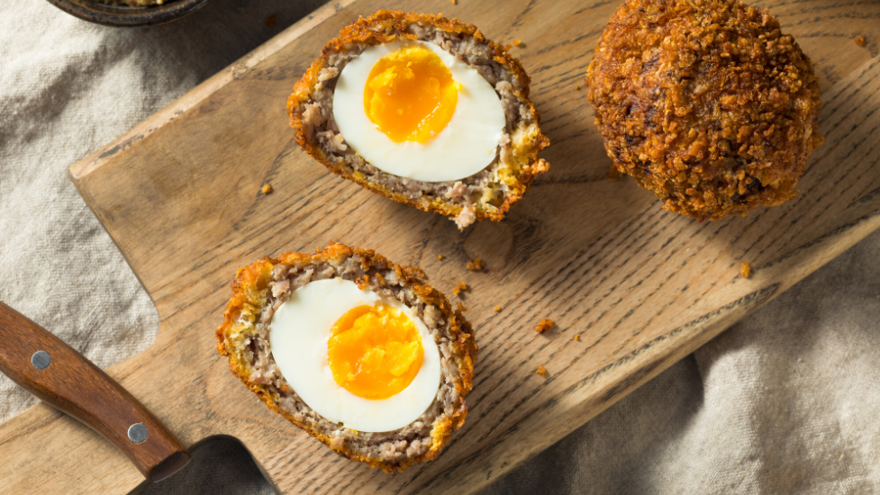 scotch eggs on top of a wooden cutting board