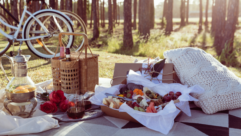 a tray of food on a picnic blanket in the woods