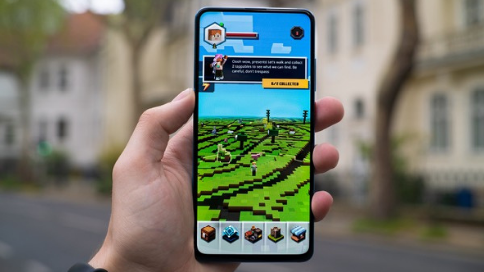 a person holding a phone with minecraft on the screen