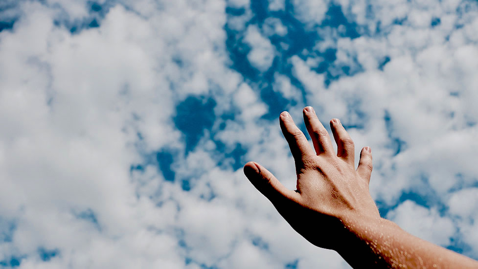 a hand holding a blue cloudy sky