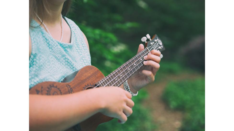 a woman holding a ukulele