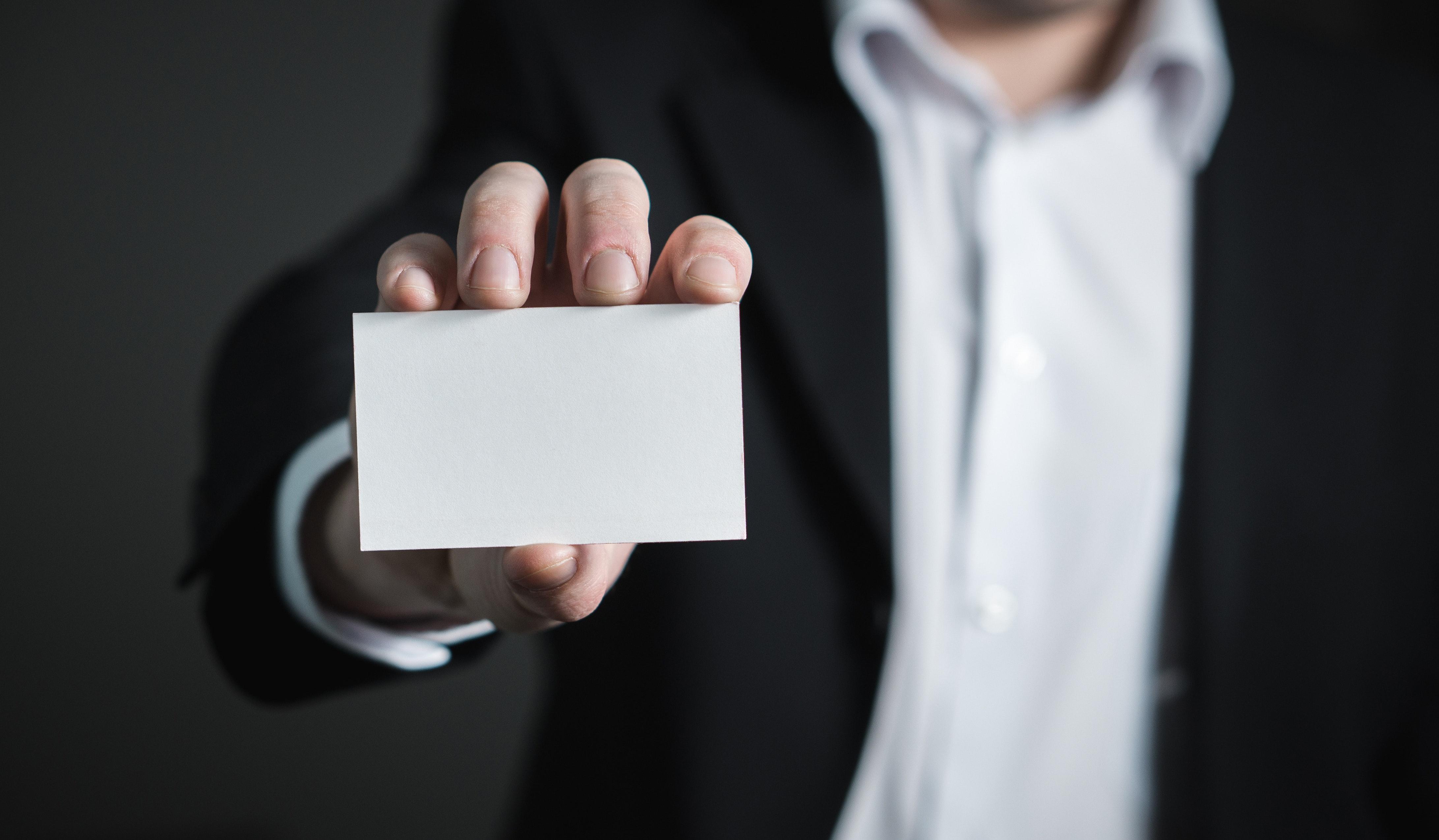 a hand holding a blank card