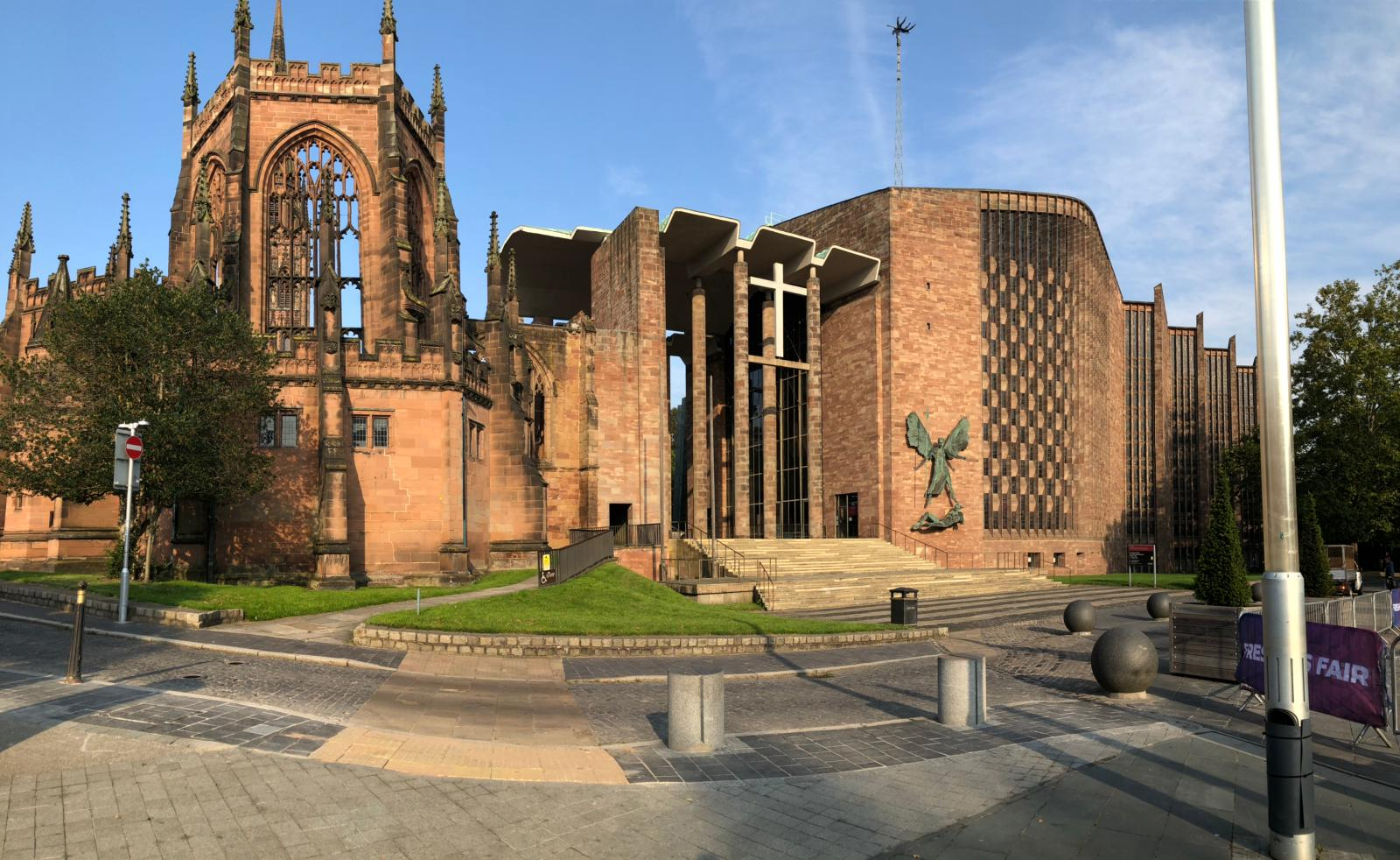 a large stone building with a clock on the side of a road with Coventry Cathedral in the background
