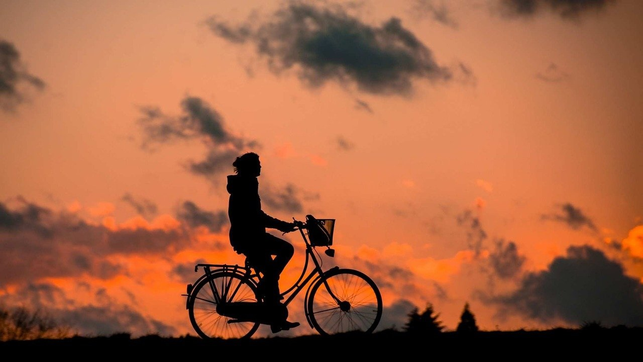 a person riding a bicycle with a sunset in the background