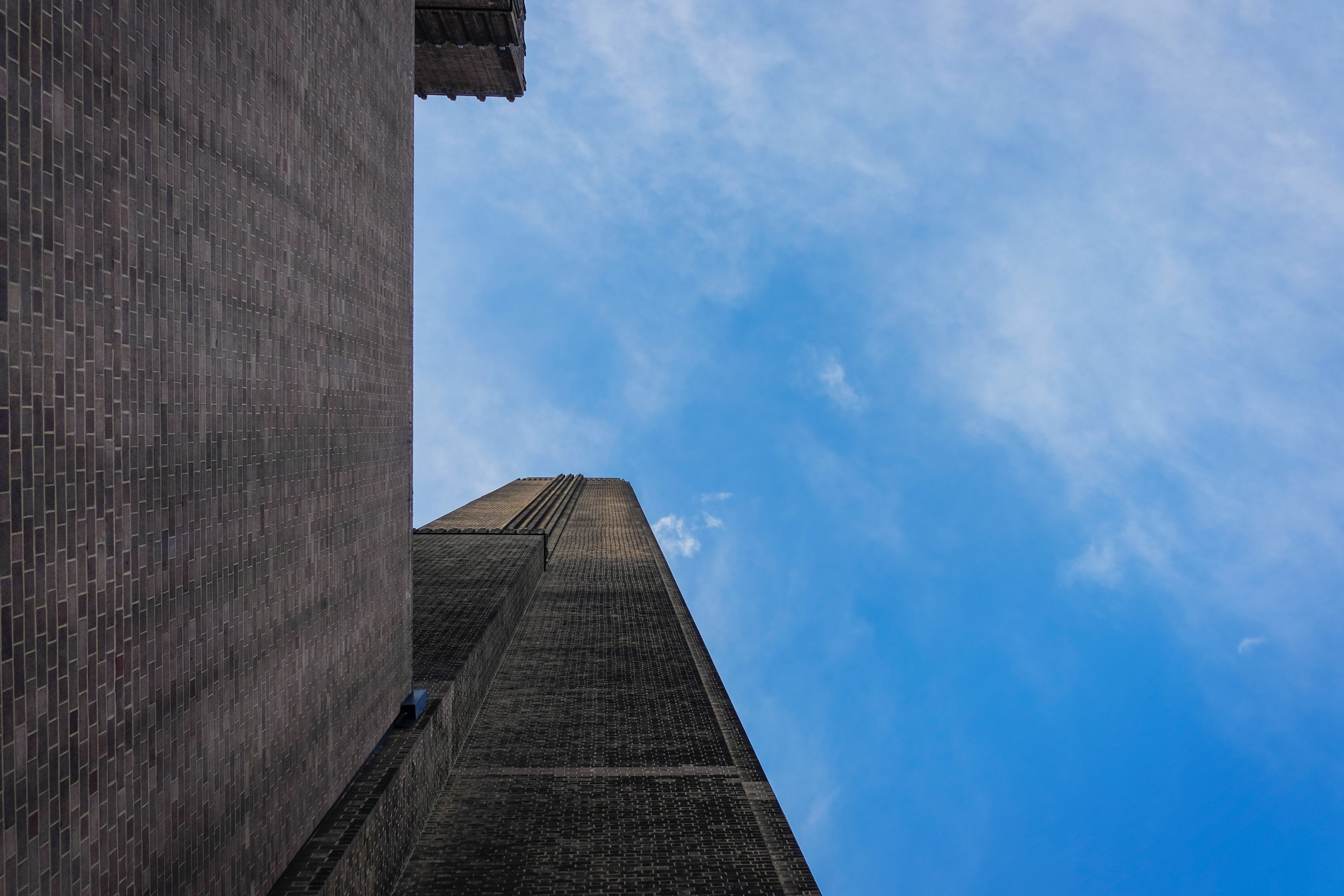 a tall brick tower with a clock on the side of a building