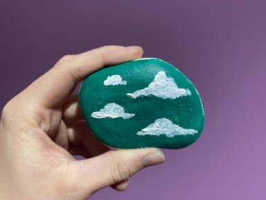 a close up stone with clouds painted on it