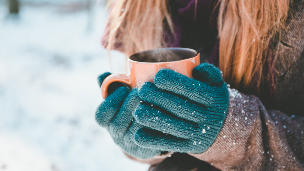 a close up of a person wearing gloves holding a mug