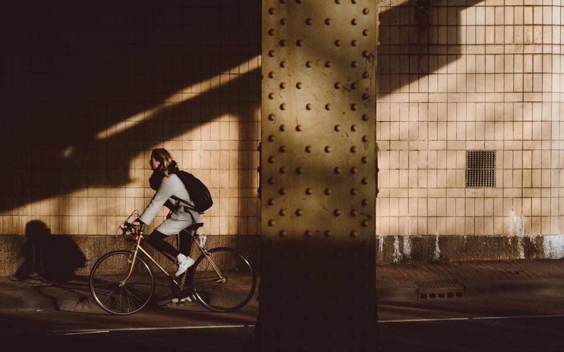 woman cycling under bridge