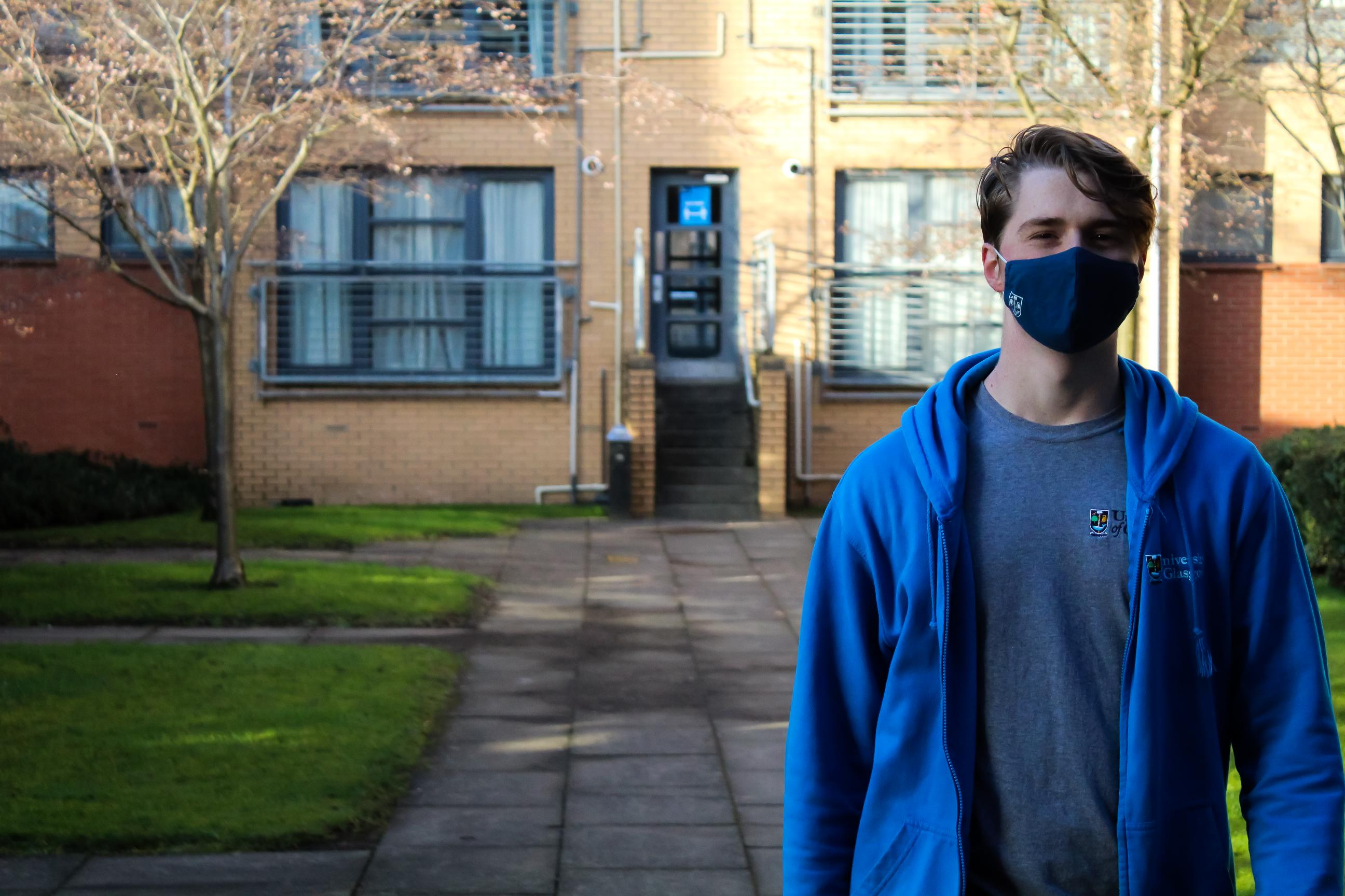 An LSA in a blue hoodie standing in front of a building