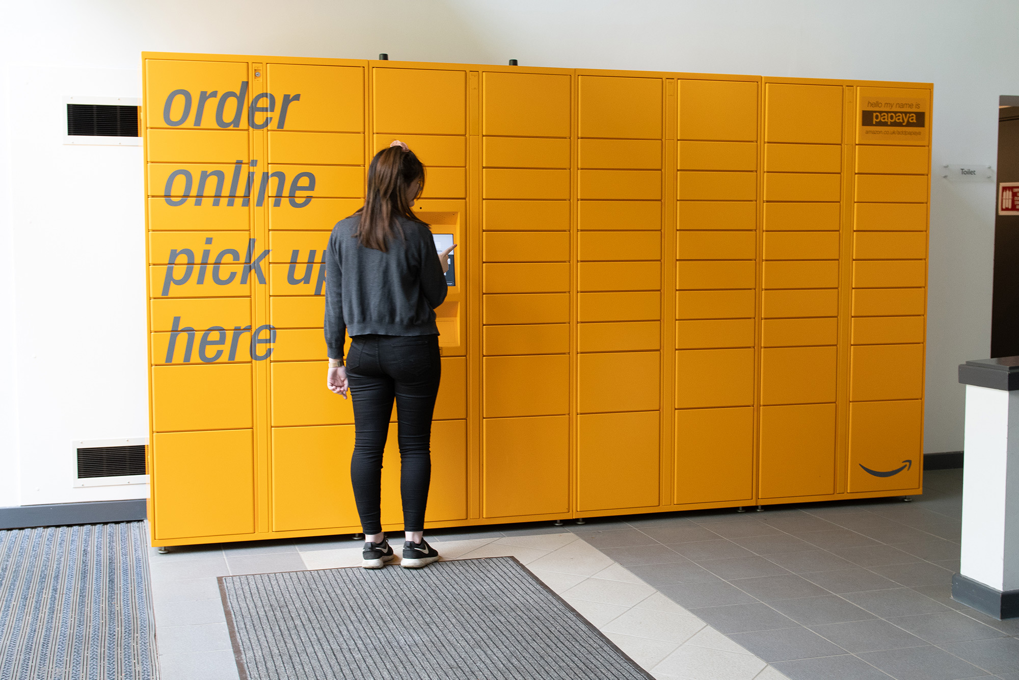 a person standing in front of an amazon locker
