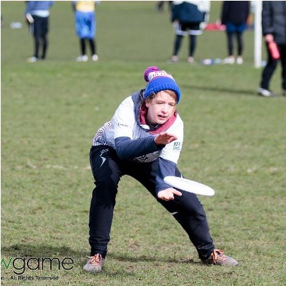 a young boy playing football on a field