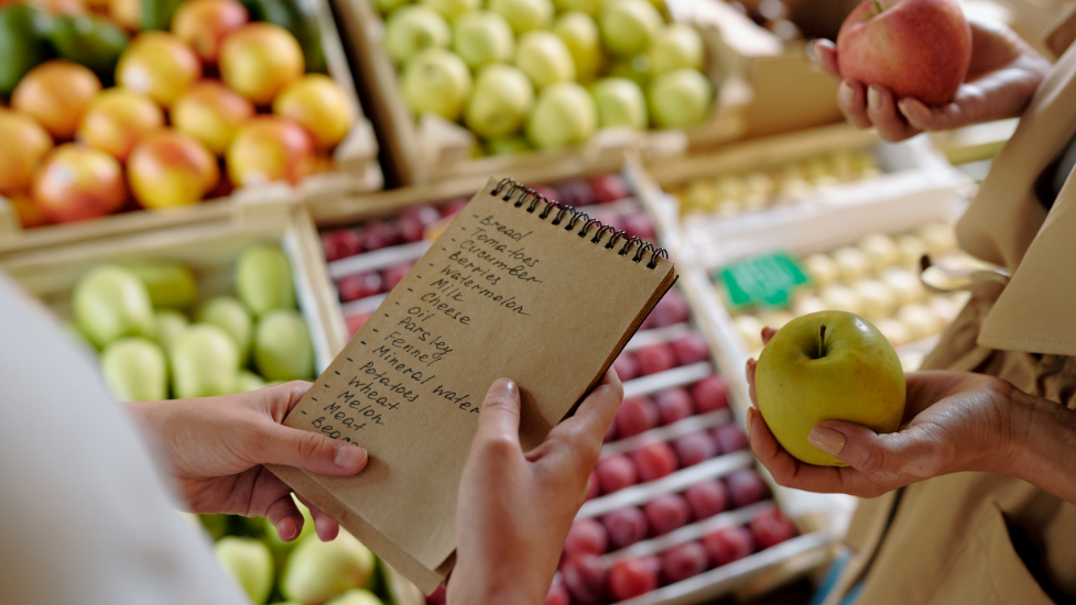a person holding a shopping list in a supermarket