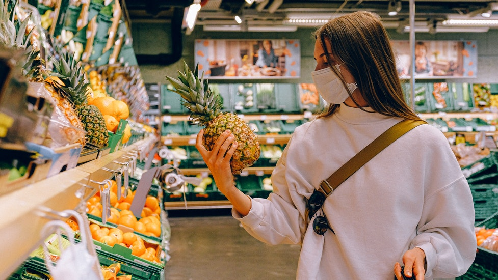 a person holding a pineapple in a supermarket