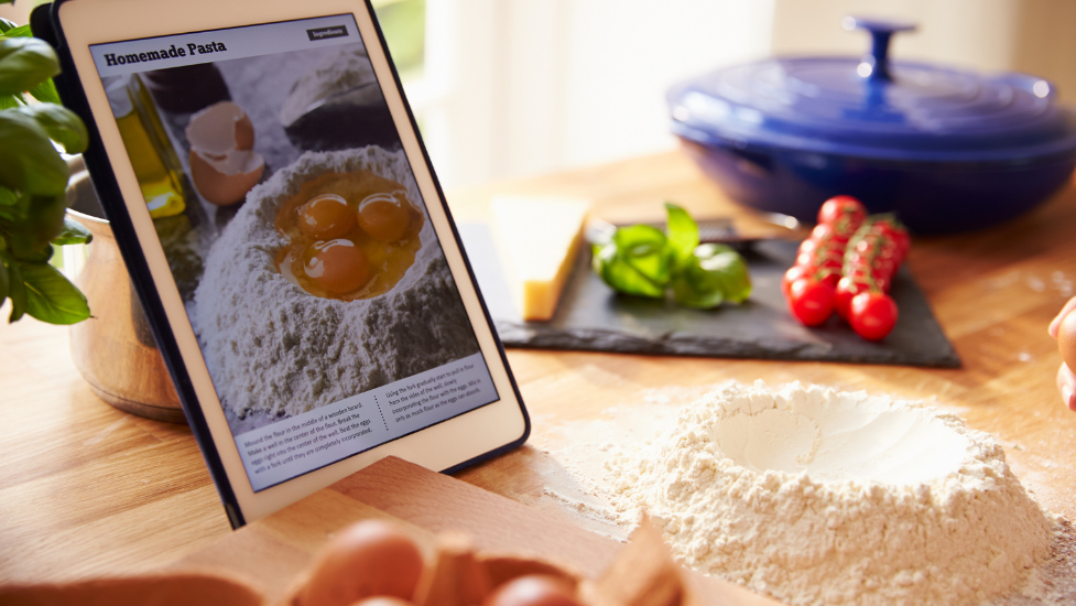 an iPad showing a recipe with flour on a work surface