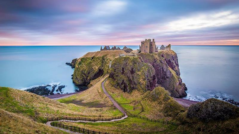 a close up of a rock near the ocean with Dunnottar Castle in the background