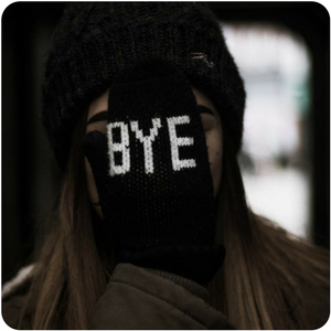 a close up of a person blocking their face with a mitten that says bye