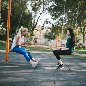 two girls sitting on swings in a park chatting