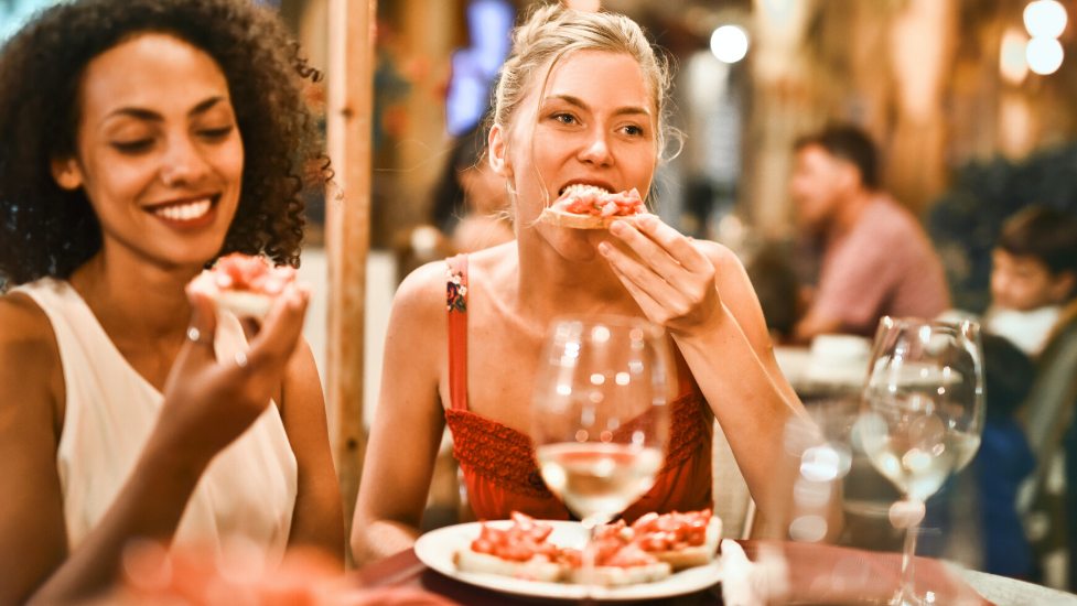 a woman sitting at a table eating food