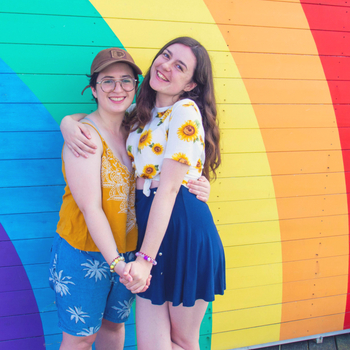 two girls standing in front of a colourful wall