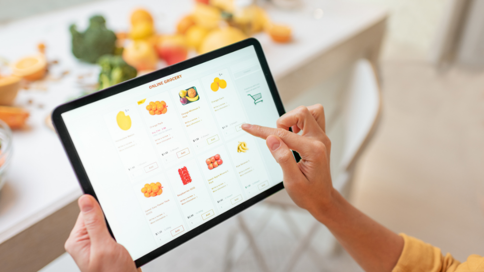 a person holding a tablet completing an online food shop