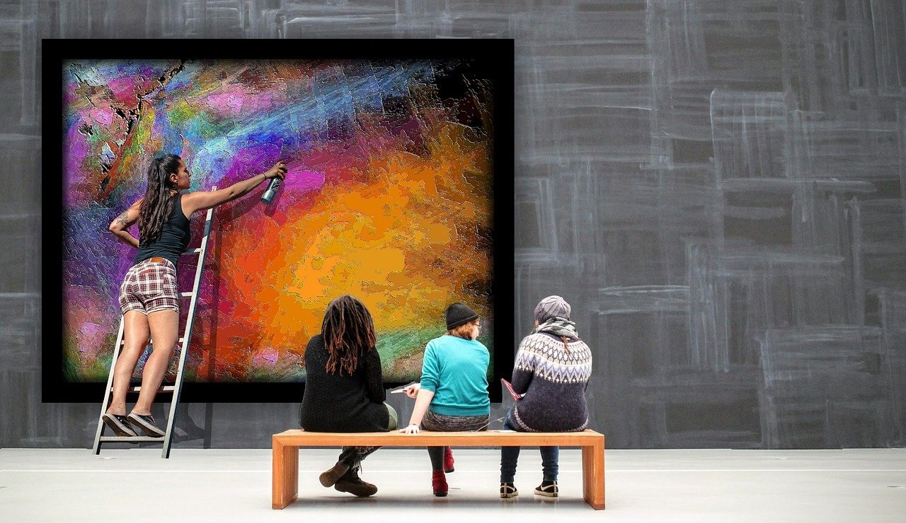 a girl painting a picture in an art gallery