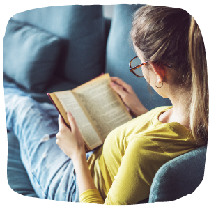 a person sitting on a couch reading a book