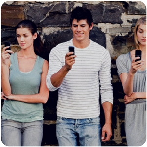 a group of people standing against a wall on their phone