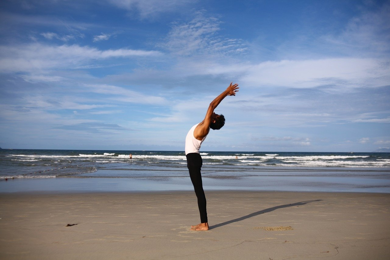 a man standing on a beach doing yoga