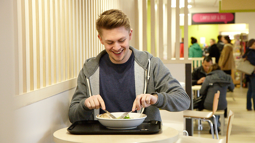 a person sitting at a table with a bowl of food