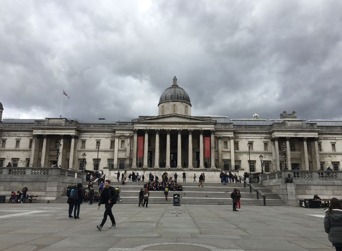 a group of people walking in front of The National Gallery