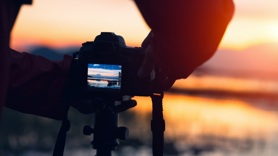 a person taking a photo of a sunset