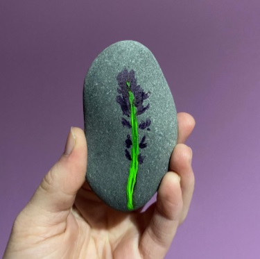 a hand holding a green and purple painted stone